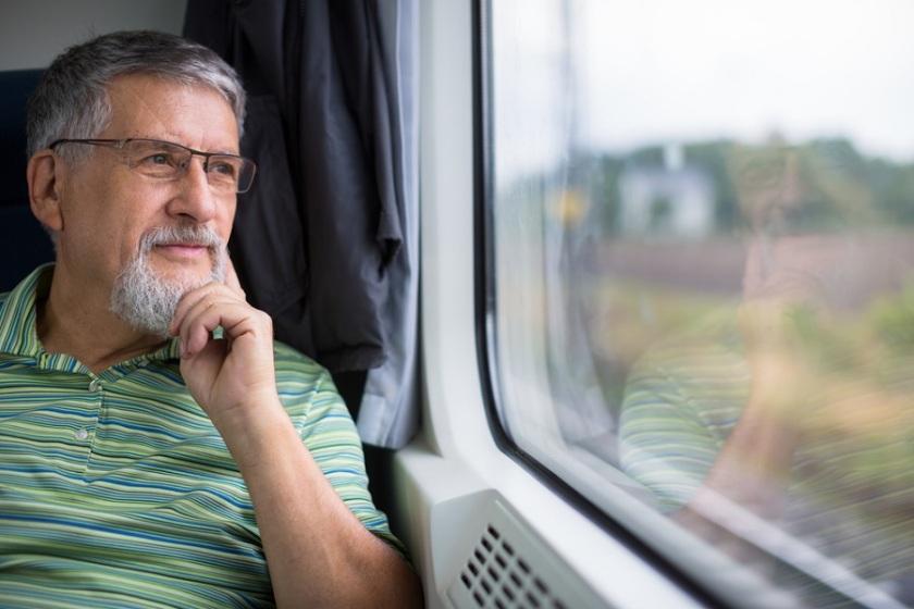 Senior man enjoying a train travel - leaving his car at home, he